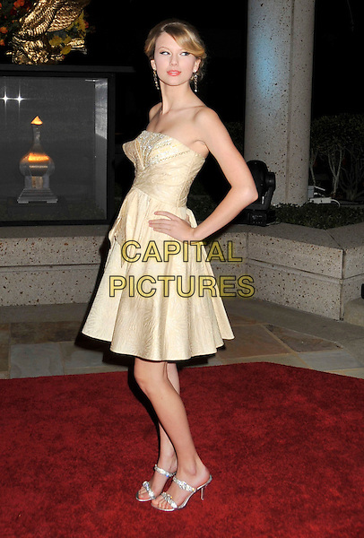 TAYLOR SWIFT.BMI's 56th Annual Country Awards held at BMI Music Row, Nashville, Tennessee, USA..November 11th, 2008.full length strapless dress gold cream hand on hip .CAP/ADM/LF.©Laura Farr/AdMedia/Capital Pictures.