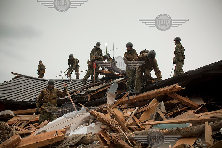 Japanese Self Defence Force (SDF) soldiers search for bodies amongst the debris. Thousands of people died in this small town which ran out of body bags. On 11 March 2011 a magnitude 9 earthquake struck 130 km off the coast of Northern Japan causing a massive Tsunami that swept across the coast of Northern Honshu. The earthquake and tsunami caused extensive damage and loss of life.
