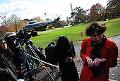 Reporters shield themselves as Marine One lands on the South Lawn of the White House in Washington, D.C. as United States President Barack Obama and first lady Michelle Obama depart the White House  on November 11, 2011.  They are leaving for a trip that will take them to California, Hawaii, and the Far East..Credit: Kevin Dietsch / Pool via CNP