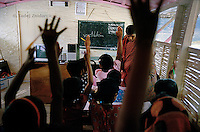 Children raise their hands to give the answer to the teacher during a class on a boat school that operates on the Atrai river. In every class there are around 30 students that come from nearby villages along the river. During a 3-hour session they study mathematics, reading and writing in Bangla and English, plus environmental subjects pertinent to their river-based life. (Photo by Tadej Znidarcic)