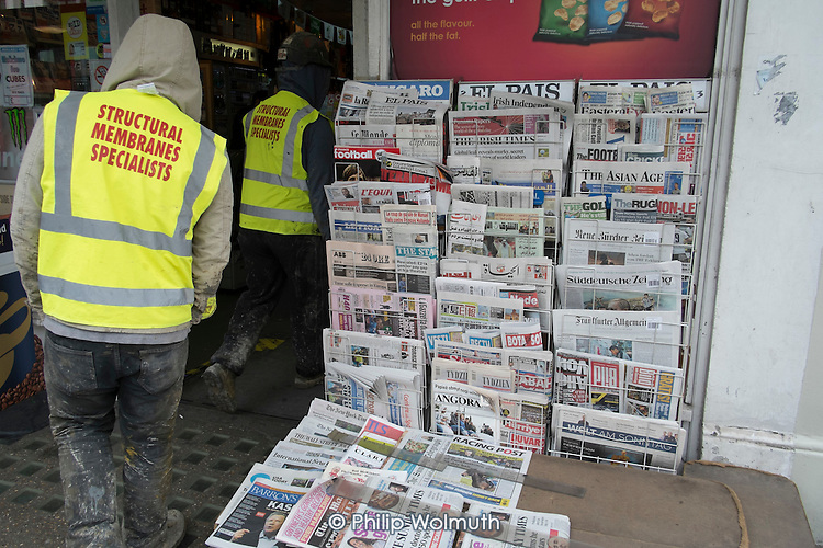Builders enter a newsagent selling foreign newspapers, Chelsea, London.