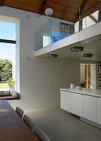 This open-plan kitchen/dining area has a living room on the mezzanine with a glass balustrade