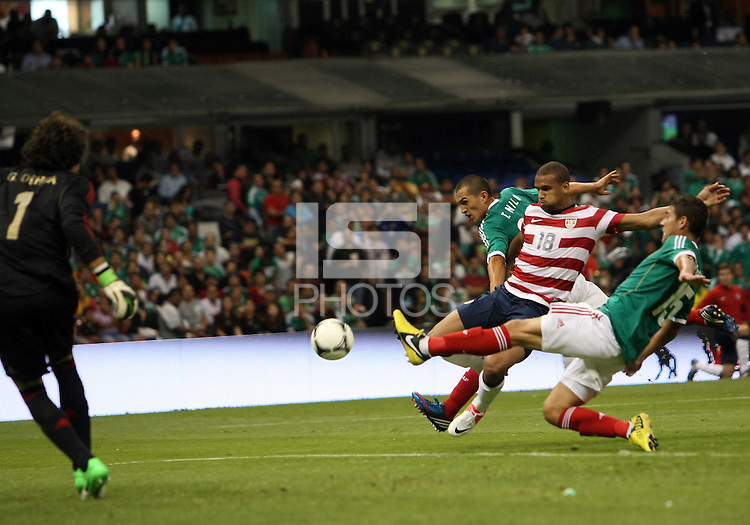 MEXICO CITY, MEXICO - AUGUST 15, 2012:  Terrence Boyd (18) of the USA MNT gets off a shot as Hector Moreno (15) of  Mexico closes in during an international friendly match at Azteca Stadium, in Mexico City, Mexico on August 15. USA won 1-0.