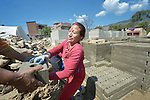 Kanchi Shrestha and other women stack blocks in Sanogoan, Nepal, that they and their neighbors will use to build new homes. This Newar community was hard hit by the April 2015 earthquake that ravaged Nepal, losing almost all their housing, but they've been helped by the ACT Alliance to rebuild their lives. The ACT Alliance has provided blankets, tents, and livelihood assistance, and is helping villagers form the tens of thousands of cement blocks they will need to construct permanent housing.