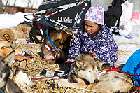 Young Angelina Hamilton pets Dallas Seavey's dog Derby as he rests on straw at the Shageluk village checkpoint during the 2011 Iditarod race.