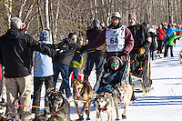 Robert Bundtzen and team run past spectators on the bike/ski trail during the Anchorage ceremonial start during the 2014 Iditarod race.<br /> Photo by Britt Coon/IditarodPhotos.com