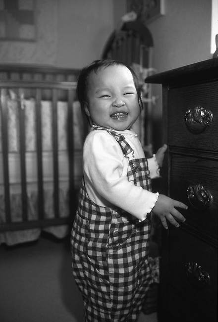 Asian-American toddler stands next to chest of drawers beside crib, Estes Park, CO