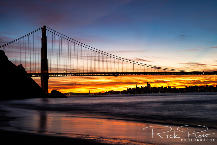 North Tower of the Golden Gate Bridge in the dawn hours with the Bay Bridge and San Francisco in the background.