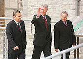 Shepherdstown, West Virginia - January 3, 2000 -- United States President Bill Clinton, center, waves to reporters in response to a question as he walks across a 200 foot-long pedestrian bridge with Prime Minister Ehud Barak of Israel, left, and Foreign Minister Farouk al_Shara of Syria, right at the start of the Israeli-Syrian Peace Talks on 3 January, 2000..Credit: Ron Sachs  / CNP