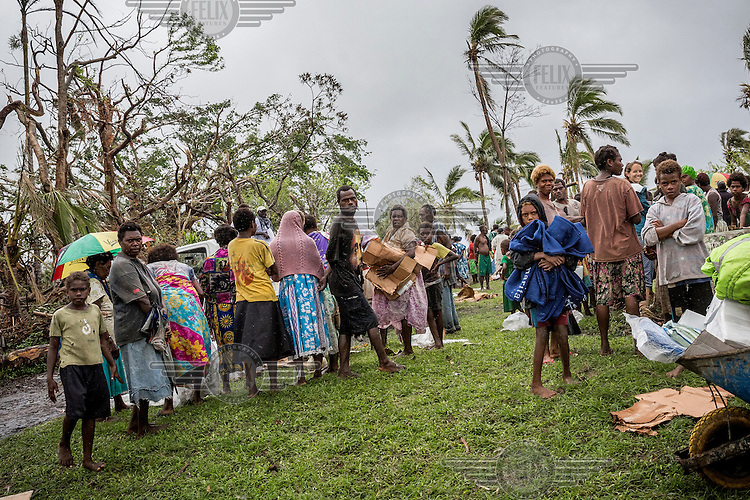 Villagers wait to receive food rations in a village on Tanna Island. The island was badly affected by Cyclone Pam and many people lost their homes and gardens and now rely on supplies from the government.<br /> Cyclone Pam, a tropical storm that hit the Pacific island nation of Vanuatu on 13 March 2015, is considered one of the worst natural disasters to affect the country. Over 15 people died in the storm and winds up to 165 mph (270 km/h) caused widespread damage to houses and infrastructure.