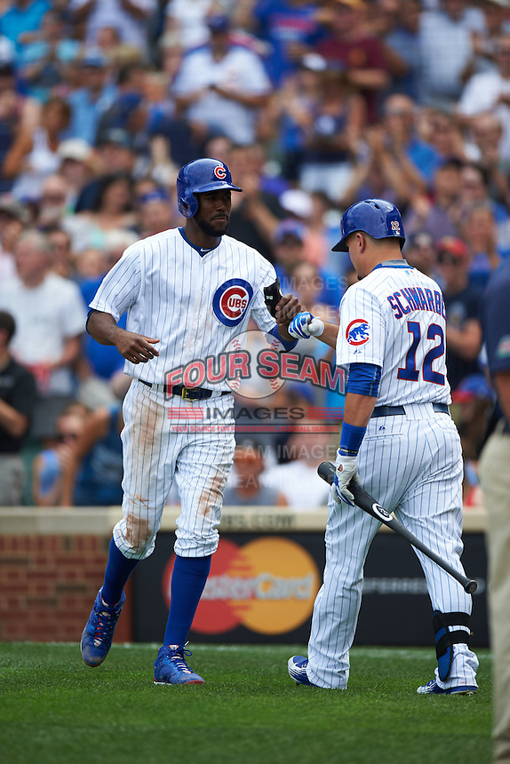 Chicago Cubs outfielder Dexter Fowler (24) fist bumps Kyle Schwarber (12) after hitting a home run during a game against the Milwaukee Brewers on August 13, 2015 at Wrigley Field in Chicago, Illinois.  Chicago defeated Milwaukee 9-2.  (Mike Janes/Four Seam Images)