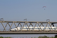 A parapenter flies over a bridge as a Shinkansen or bullet train is passing. Kurami, Kanagawa, Japan. Monday June25th 2018