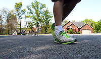 STAFF PHOTO SAMANTHA BAKER &bull; @NWASAMANTHA<br /> Sowers goes on a two-mile run with his dog, Louie, Friday, May 2, 2014, in Fayetteville. Audiss says Sowers is very hard on shoes because of the way he walks and runs. She estimates he goes through four pairs of shoes a year.