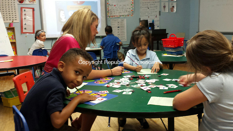 WATERBURY -- Regan Elementary School kindergarten students (left to right) Octavio Bonilla, Vanessa Viera and Tatiana Crosi, work on a math lesson with teacher Michele Parks Friday. Regan is one of several city schools to show particularly strong gains in recently released district reading and math assessments.
