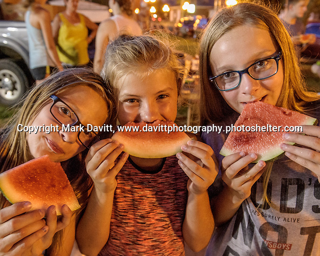 Alex Sagar, Kennadi Fulmer and Sami Sagar cool off with watermelon at the Polk County Fair July 21. The watermellon was welcome relief on the hot evening and was provided after the beef show by Beattie Melon Patch of Runnels.