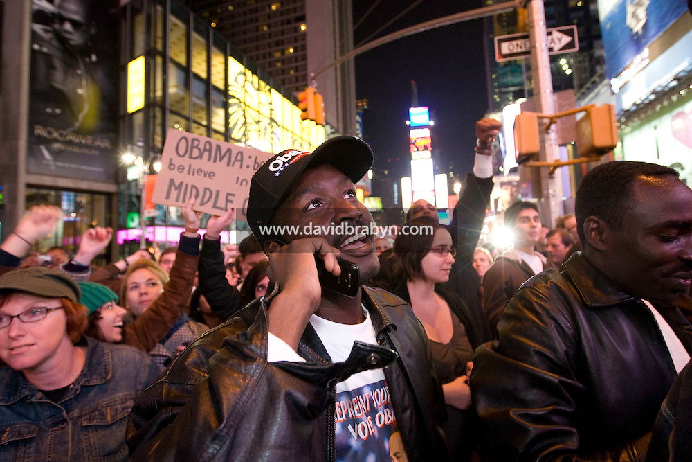 People watching television coverage of the 2008 US presidential election results on a giant screen on Times Square in New York, NY, United States, celebrate as Barack Obama's favorable results come in, 4 November 2008.