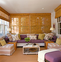 Rolled split-bamboo blinds and a hand-painted sisal rug complete the contemporary look of this sun room decorated in lavender, purple and acid green