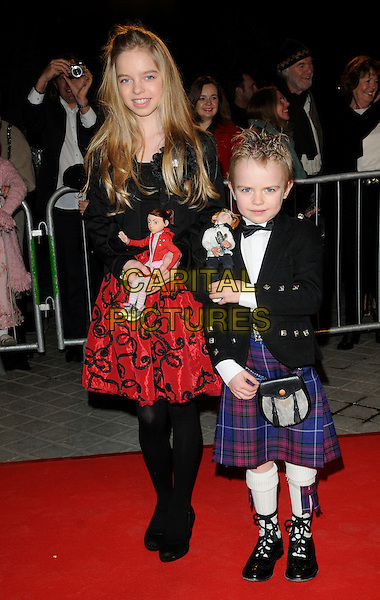 "KIZZY MEE & JAMIE MUNNS .At the UK Film Premiere of ""The Flying Machine"", Royal Festival Hall, Southbank, London, England, UK, February 12th 2011..full length kilt dolls red dress black tights jacket  bow tie .CAP/CAN.©Can Nguyen/Capital Pictures."