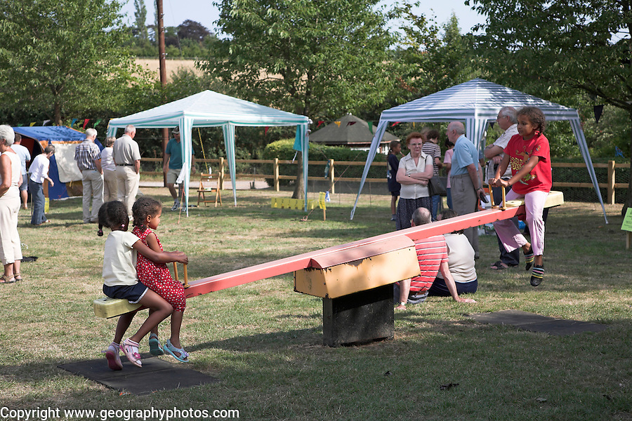 Children play on See-saw, Hasketon Village summer fete, Suffolk, England