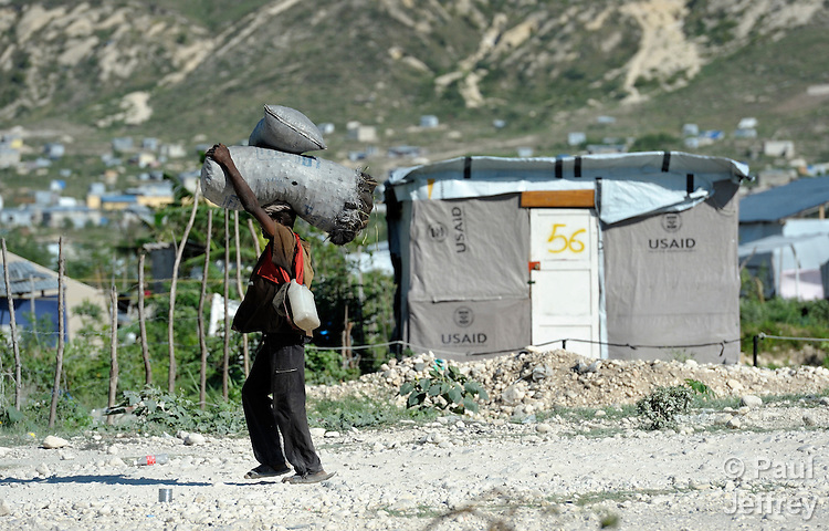 A man carries bags of charcoal in a squatter settlement area outside Camp Corail, a controversial resettlement of earthquake survivors north of Port-au-Prince, Haiti. Thousands of families were relocated to Corail from flood-prone areas of the capital in 2010, yet the promises of jobs that lured them there failed to materialize.