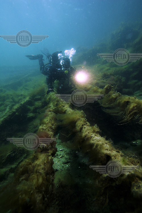 Diver explore water and sewage pipe lines. As they are wrapped with led to hold them down, the pipes pose a threat to the environment. Pollution, in the form of dissolved led, will be affecting the waters, ground and animals. Diving.