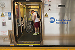 During evening rush hour, passengers, including a man with a bicycle, are in a train car with door open at Merrick train station of Babylon branch, after MTA Metropolitan Transit Authority and Long Island Rail Road union talks deadlock, with potential LIRR strike looming just days ahead.
