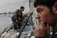 A Free Syria Army (FSA) soldier keeps an eye out for regime forces as they plan to attack and neutralize a tank positioned on the street ahead in the Karmel Jabl front of Aleppo city on October 31, 2012. Both FSA and civilian casualties mounted during the day as combat resumed after a U.N. - negotiated truce (which was not respected by either side). Regime snipers inflicted heavy casualties on Free Syria Army forces as both sides mounted attacks on each other. The skies of Aleppo were again filled with the sound of aerial bombing and artillery fire. ..© AFP/Javier Manzano............................