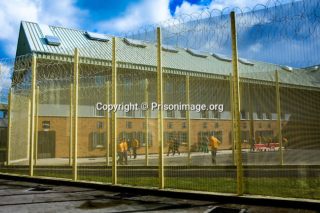 Prisoners walking around the exercise yard of one of the housing blocks. HMP Holme House is a large purpose built category B local prison for male adult prisoners, opened in 1992,who are either remanded in custody or convicted. It has capacity to hold 1212  prisoners. The prison is operated by Her Majesty's Prison Service.