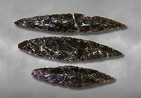 Black obsidian blades. Catalhoyuk Collections. Museum of Anatolian Civilisations, Ankara. Against a gray mottled background