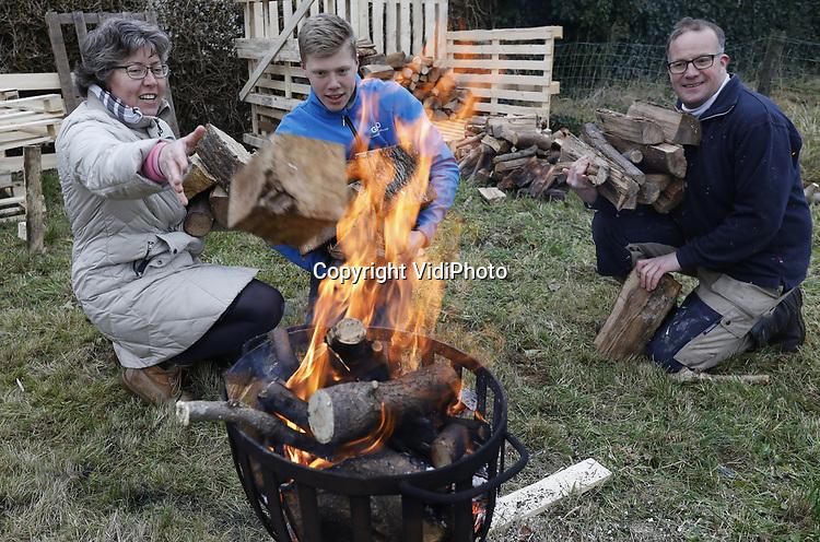 Foto: VidiPhoto<br /> <br /> VALBURG &ndash; De familie Boom uit Alblasserdam maakt zich vrijdag op voor hun verhuizing naar Valburg in de Betuwe. Eerst vertrekt de houtvoorraad en komend voorjaar volgt de rest van de inboedel. Om zichzelf tijdens het stapelen van de houtblokken op hun nieuwe bouwkavel warm te houden, brandt gezellig de vuurkorf. De familie verhuist naar Gelderland omdat grond en woningen daar nog betaalbaar zijn, in tegenstelling tot West-Nederland. Rust, betaalbare ruimte en een goede infrastructuur is de reden dat Gelderland ook het afgelopen jaar behoorde tot een van de populairste groeiprovincies. Door de aanleg van een railterminal en de komst van diverse distributiecentra naar de Over-Betuwe neemt bovendien de werkgelegenheid fors toe. Dat overigens wel ten koste van rust en ruimte...