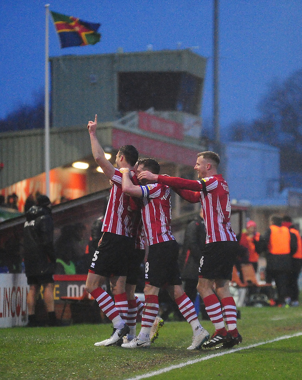 Lincoln City's Jason Shackell, left`, celebrates scoring his side's third goal with team-mates<br /> <br /> Photographer Andrew Vaughan/CameraSport<br /> <br /> The EFL Sky Bet League Two - Saturday 15th December 2018 - Lincoln City v Morecambe - Sincil Bank - Lincoln<br /> <br /> World Copyright © 2018 CameraSport. All rights reserved. 43 Linden Ave. Countesthorpe. Leicester. England. LE8 5PG - Tel: +44 (0) 116 277 4147 - admin@camerasport.com - www.camerasport.com