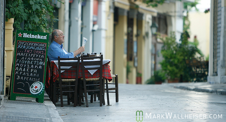 A merchant sits at his tables and reads the morning paper in one of the streets of Athens, Greece.