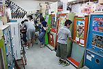 Tokyo, Japan - Visitors play with retro game machine at the Traditional Sweet Shop and Game Museum in Tokyo, June 16, 2013. The Traditional Sweet Shop and Game Museum opened in 2009 to introduce the Japanese retro sweets and games to visitors who can play with 10 yen (10 cents USD). According to the owner some machines are from 1970. The Museum also rents the machines to movies and TV programs. It received a Citizen's Culture Special Award from Itabashi Ward. (Photo by Rodrigo Reyes Marin/AFLO)