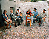 GREECE, Patmos, Diakofti, Dodecanese Island, family and friends play music and dine by the Agean Sea at Diakofti Taverna
