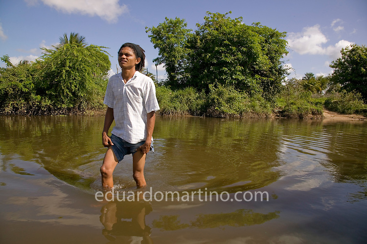 Elias Lins dos Santos, Palmalimpe's manager, crosses the river between the area where he lives in Conjunto Palmeiras and Palmas Bank, where Palmalimpe is located. Now a bridge is being built, saving him to get wet to reach work and to go back home; until very recently that was his daily routine..Fortaleza, Ceara, Brazil.Photo: Eduardo Martino / Documentography