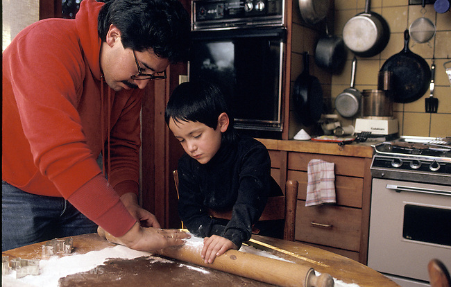 Berkeley, CA Latino father helping  son around five-years-old to make cookies
