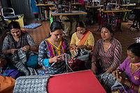 Nepal, Kathmandu, Kokhana. The nonprofit Sabah, running a clothing making business to help women workers. Women sewing and knitting Sherpa Adventure gear, a Nepal brand exported to Europe. These women prefer to work as a community rather than alone in home based work. Model released