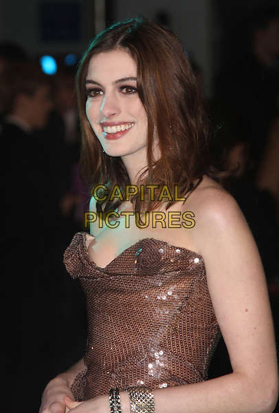 "ANNE HATHAWAY.Arriving at the World Royal Film Premiere of ""Alice In Wonderland"", Odeon cinema Leicester Square, London, England, February 26th 2010..arrivals half length strapless sequined brown sequin bronze  bustier dress Vivienne Westwood bracelets cuff smiling profile side .CAP/AH.©Adam Houghton/Capital Pictures."
