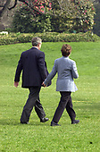 United States President George W. Bush holds hands with first lady Laura Bush as they walk across the South Lawn of the White House in Washington, DC to Marine 1 on April 6, 2001.  They were departing the White House for Milwaukee, Wisconsin where the President was to throw out the first ball at the Milwaukee Brewers vs. Cincinnati Reds baseball game.<br /> Credit: Ron Sachs / CNP