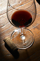 A glass of red wine with a cork stamped with the name of the chateau on an old wooden table top tabletop Chateau Thieuley La Sauve Majeure Entre-deux-Mers Bordeaux Gironde Aquitaine France