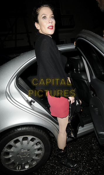 """ANNA FRIEL.Seen leaving the theatre after her evening performance of """"Breakfast At Tiffany's"""", Theatre Royal Haymarket, London, England, UK,.November 21st 2009..full length red dress black biker boots long cardigan bare legs getting into car .CAP/CAN.©Can Nguyen/Capital Pictures"""
