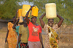 Women carry water to their homes on April 12, 2017, in Dong Boma, a Dinka village in South Sudan's Jonglei State. Most of the villagers recently returned home after being displaced by rebel soldiers in December, 2013.<br /> <br /> The women obtained water from a well drilled by the Lutheran World Federation, a member of the ACT Alliance, which is helping villagers restart their lives with support for housing, livelihood, and food security.