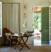 Pale green shutter doors open out from this guest bedroom to a terrace beyond