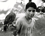 August, 2005. A young boy with his parrot.  The surfing village of Troncones, in Guerro, Mexico.