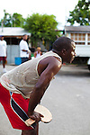 "Originating in Barbados in the 1930s, Road Tennis is played in on the back streets and roads of the country or now in permanent courts, such as the ones in Oistins and Speightstown.  The game is played on a 10x20 foot court and the ""net"" is an 8 inch by 10 foot piece of wood.  It has the same rules as table tennis (ping pong) and is a 21 point game.  It uses hand hewn rackets made largely from plywood and tennis balls that have had the fur removed.  It is the only endemic sport to Barbados and is wildly popular among the local population.  Pictured here is a road tennis court in the back roads of the countryside."