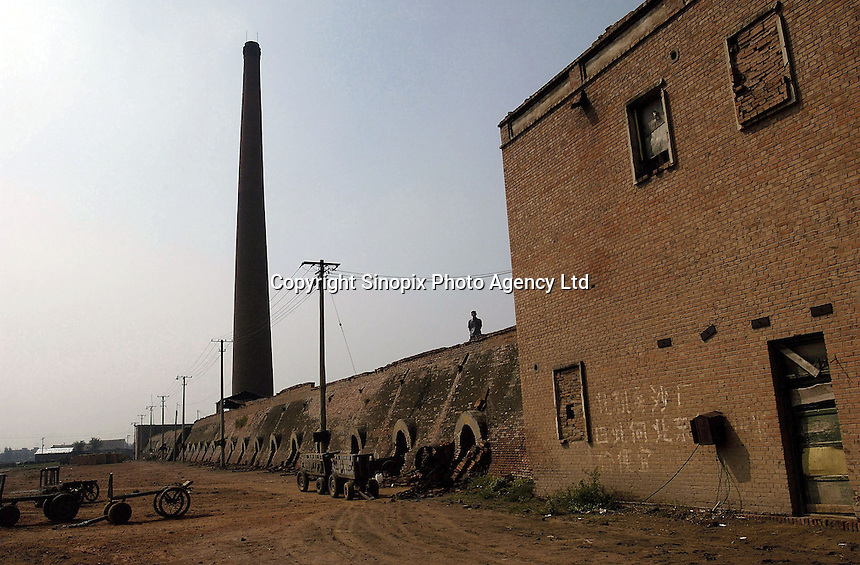 A brickkiln in Bazhou, Hebei province, China. The brickkiln was built during Mao the Great Leap Forward campaign in 1958. With a rapid ecomomic growth in China, more than 120,000 bricks are made from the brickkiln  per day nowdays, though clay bricks has been prohibited from using in more than 170 cities of China since 2002 to protect the fertile land..04-SEP-04