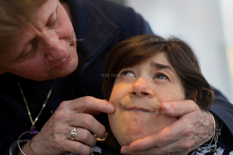 Maureen Kacinski interacts with her daughter Teresa Kacinski, 46,  in one of the residences in Malone Park at the Fernald Developmental Center in Waltham, Massachusetts, USA.  Teresa is confined to a wheelchair, cannot speak, and needs to have her hands restrained when she is awake. Teresa is the youngest resident at the center.