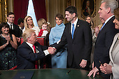 United States President Donald Trump turns to US House Speaker Paul Ryan (Republican of Wisconsin) as he is joined by the Congressional leadership and his family as he formally signs his cabinet nominations into law, in the President's Room of the Senate, at the Capitol in Washington, Friday, Jan. 20, 2017. <br /> Credit: J. Scott Applewhite / Pool via CNP