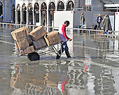 A delivery person walks through flooded St. Mark's Square in Venice, Italy in the morning of Thursday, October 21, 2010.  The morning is Venice is some of the earliest in memory..Credit: Ron Sachs / CNP