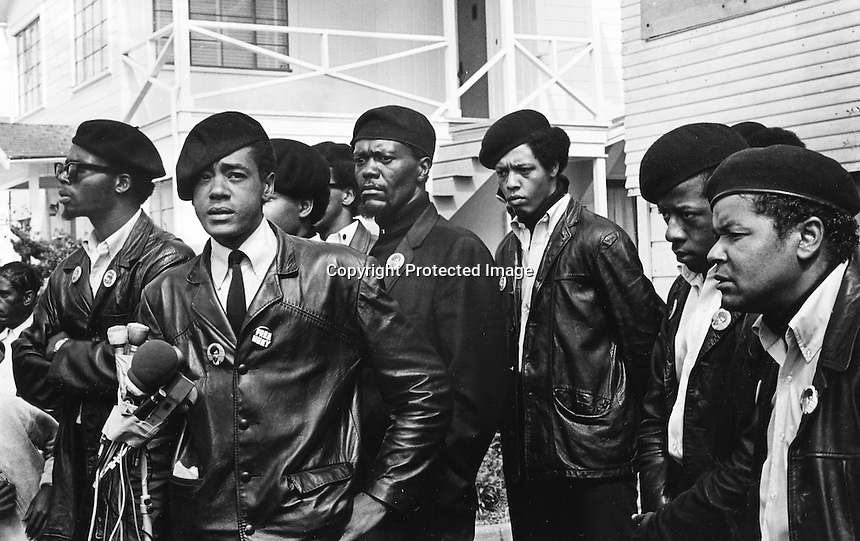 Black Panther press conference in Oakland, Ca  after the shooting of one of their members 17-year old Bobby Hutton. Hutton was shot by Oakland Police when he and Panther Elridge Cleaver were envolved in a shootout with police. (center)at microphones is  Bobby Seale, and behind his left shoulder is William Lee Brent. (1968 photo by Ron Riesterer)copyright @2014